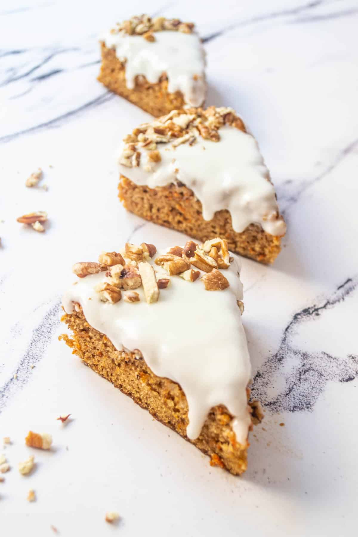 Several slices of dairy free carrot cake on a table.