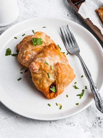 Two egg puffs on a plate with a fork.
