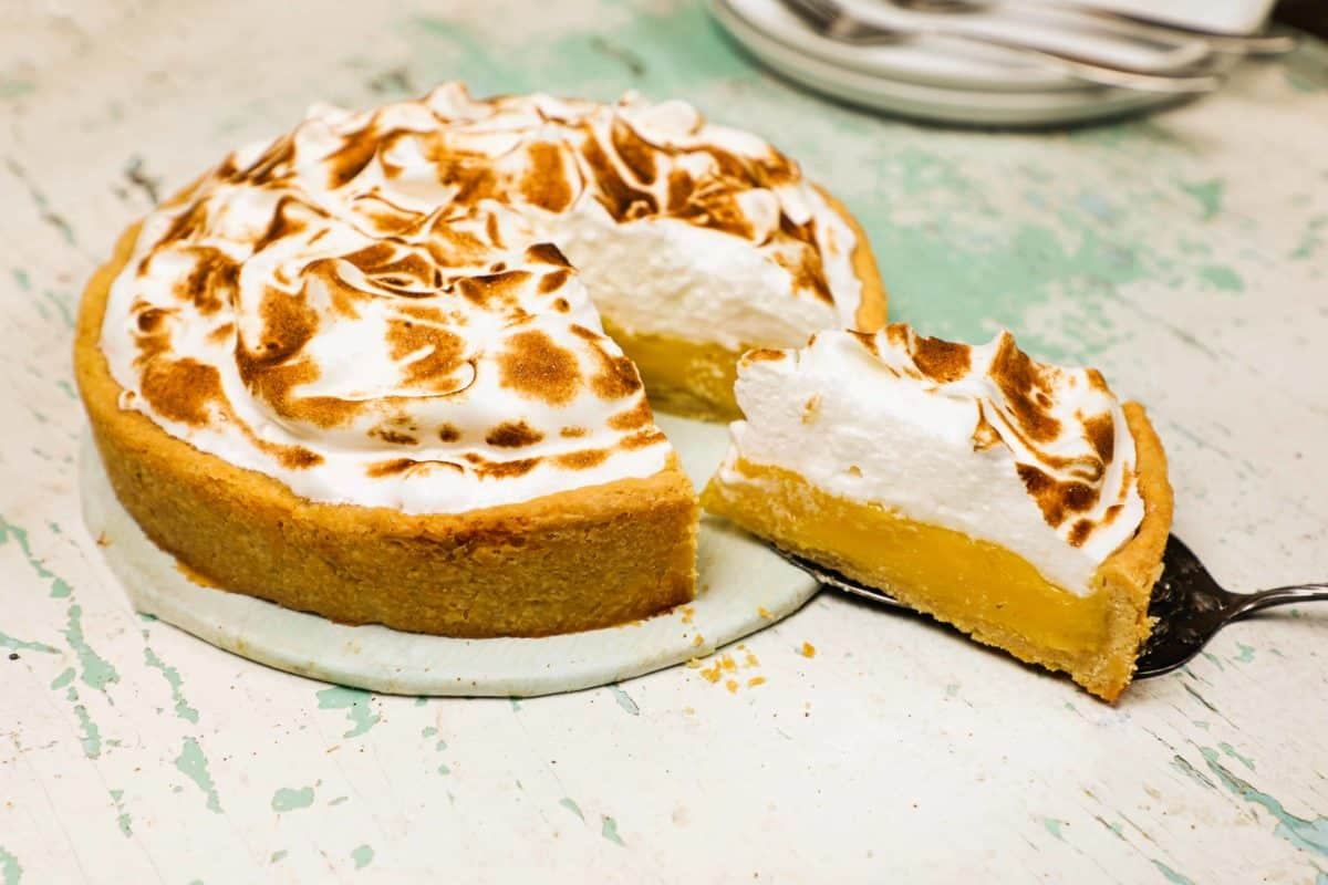 A slice of lemon meringue pie being served with a cake server.