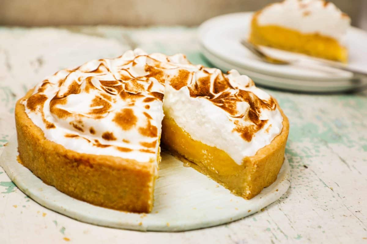 A lemon meringue pie on a table with a slice cut out of it.