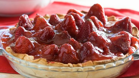 A finished strawberry pie in a pie dish.