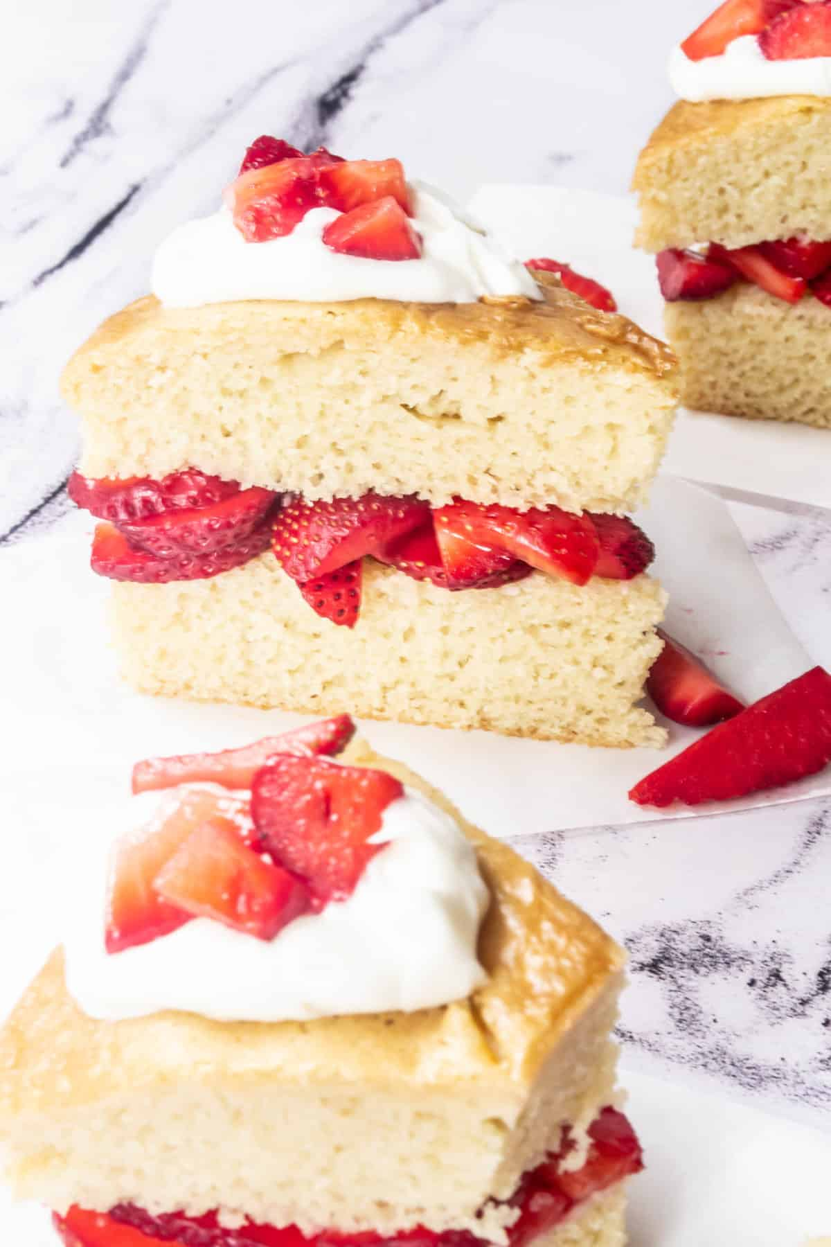 Layered strawberry shortcake topped with fresh strawberries and whipped cream.