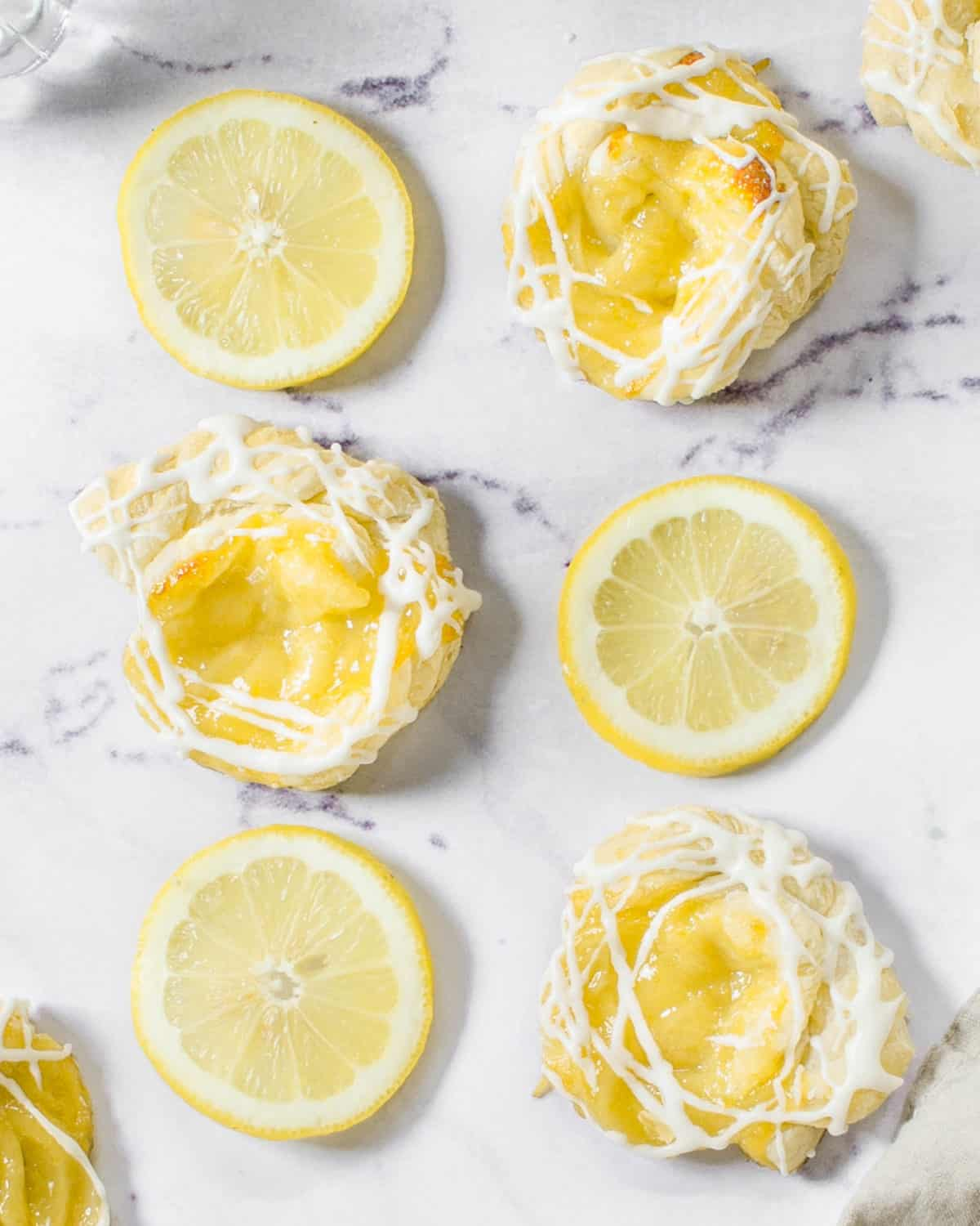Lemon curd puff pastries spread out on a table with lemons.