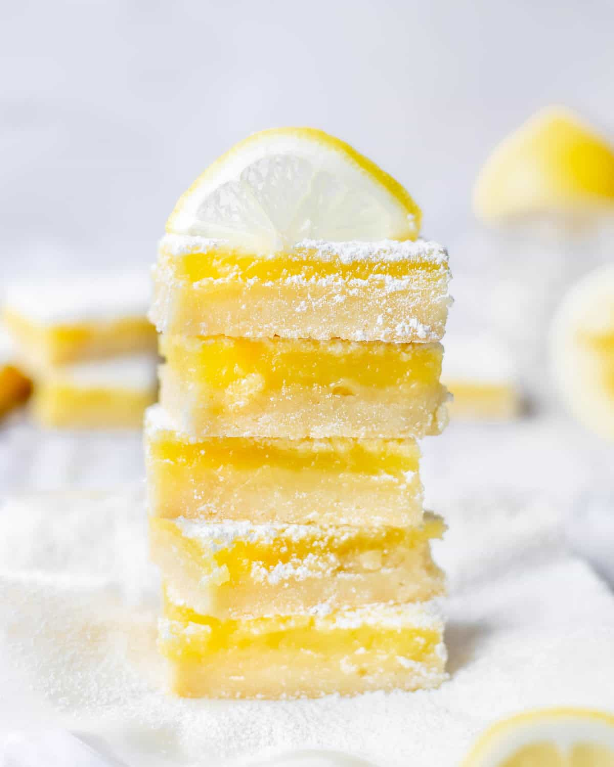 A stack of Meyer lemon bars topped with a lemon.