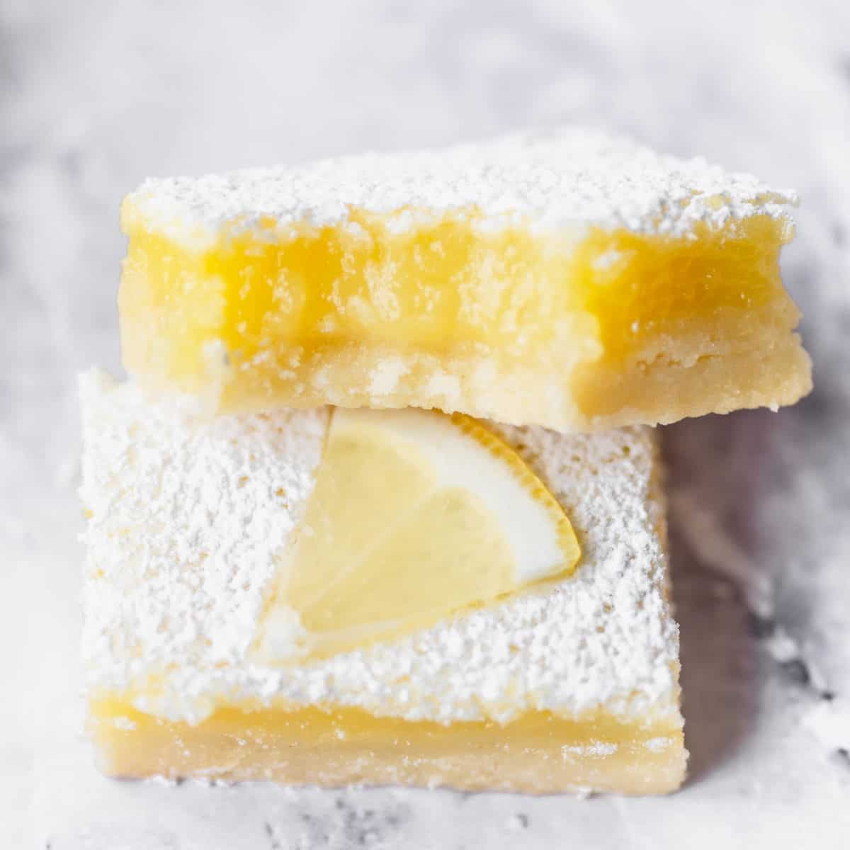 A lemon bar up close with a bite taken out of it.