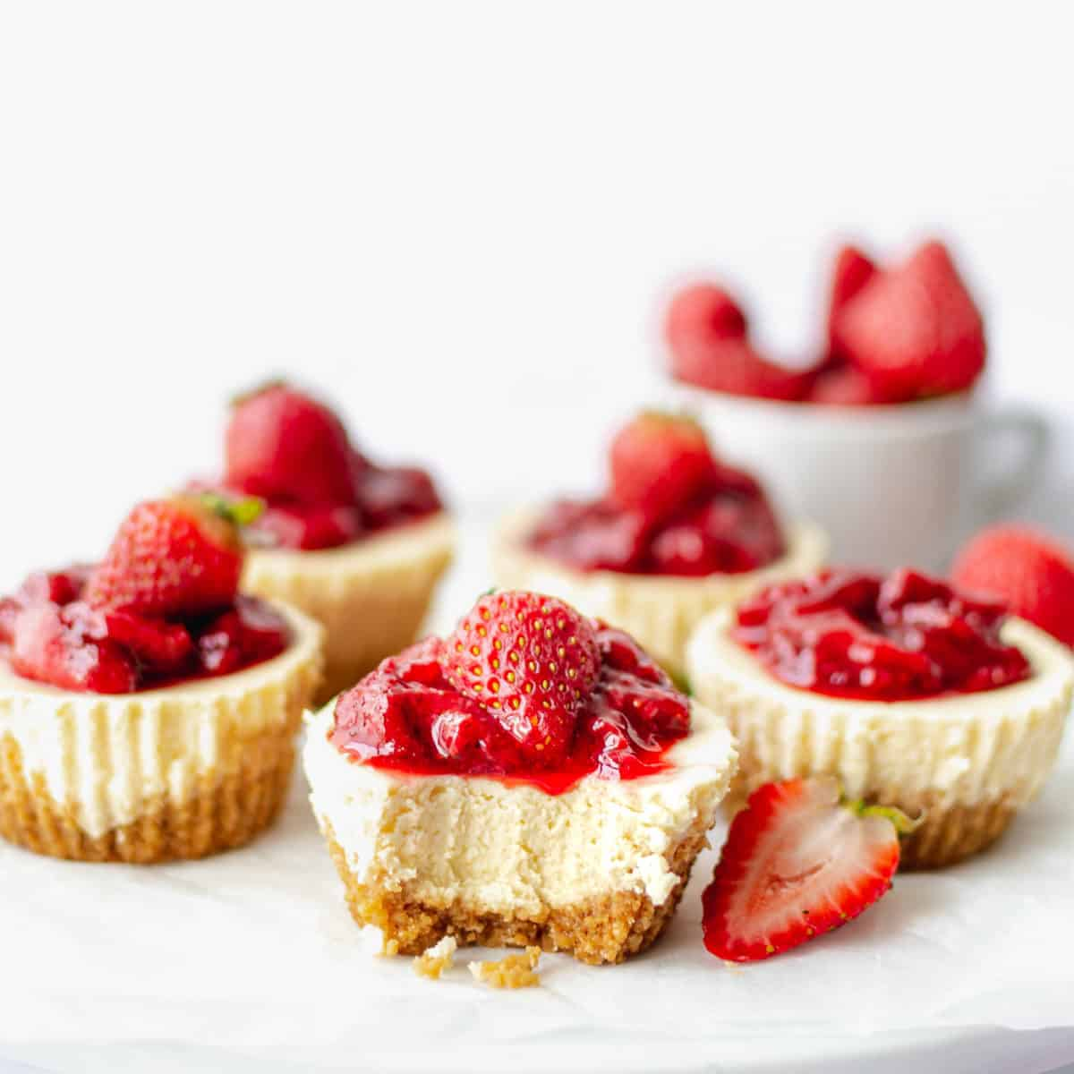 A mini strawberry cheesecake with a bite taken from it.