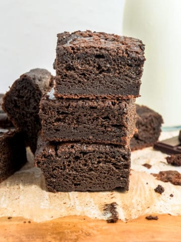 A stack of three mochi brownies on top of a wooden board.