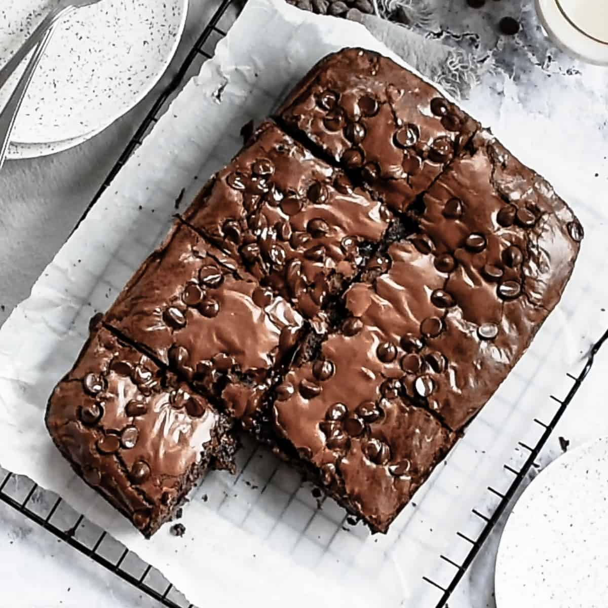 Brownies on a cooling rack with one already cut out and missing.