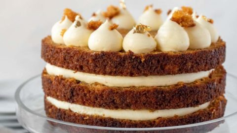 A three-layer carrot cake complete on a cake stand.