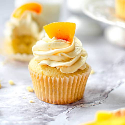 Close up of cupcake topped with a fresh peach.
