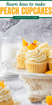 Several cupcakes on display with a glass of milk in the background.
