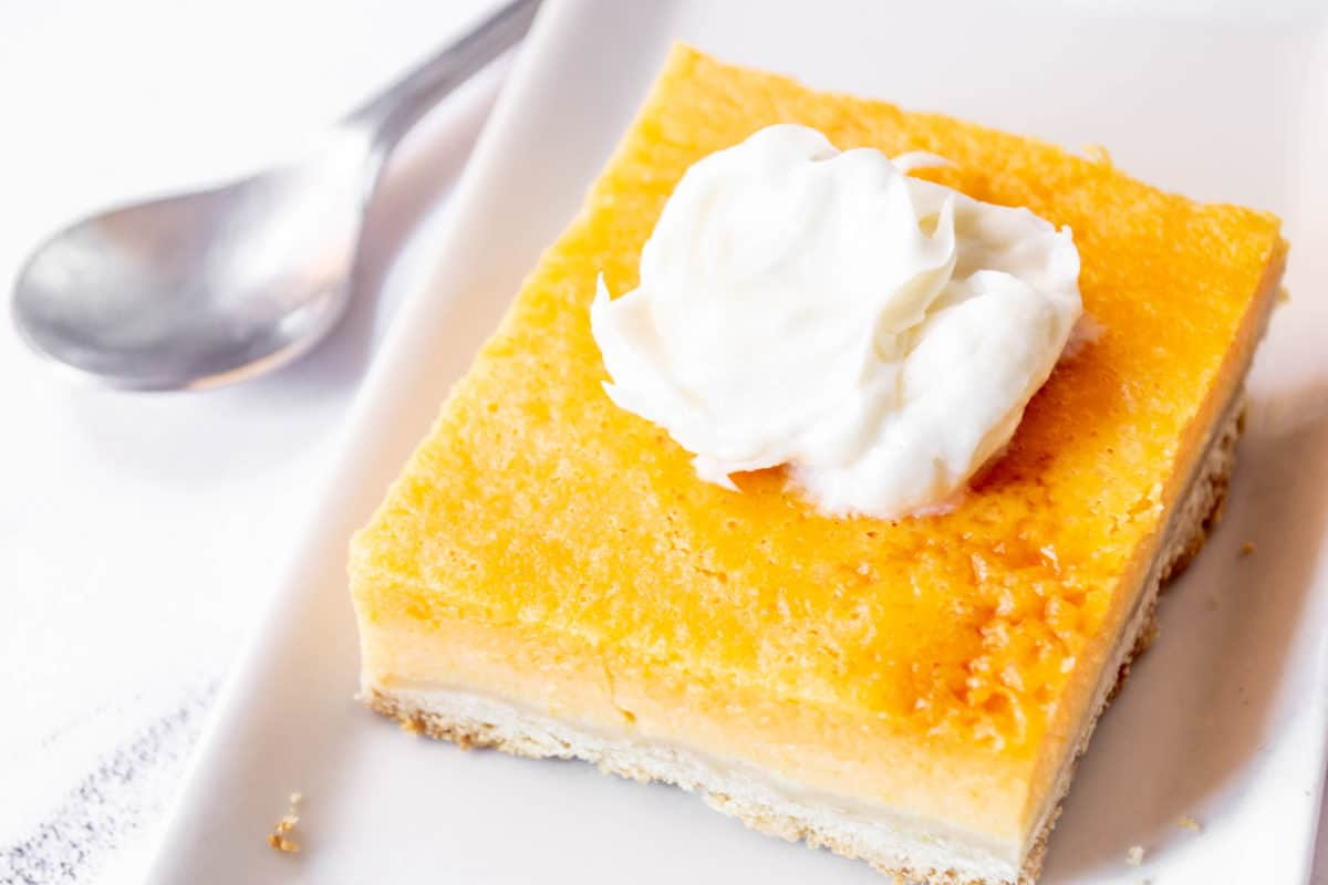 A square pumpkin pie bar on a plate topped with whipped cream.