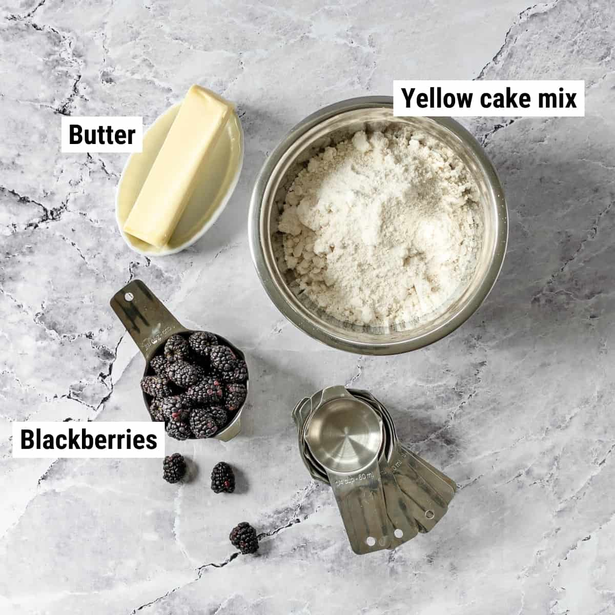 The ingredients to make blackberry cobbler with cake mix laid out on a table.