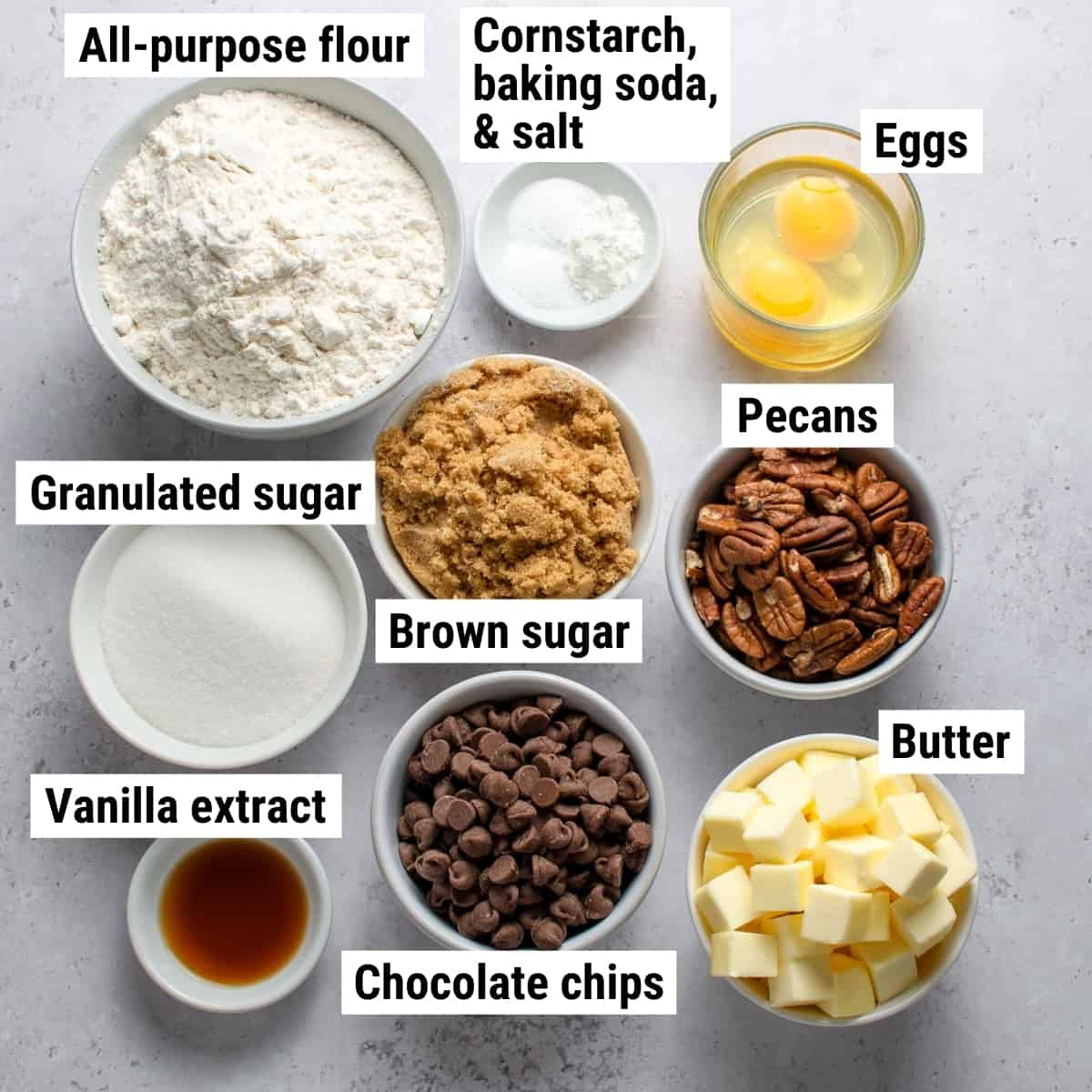 The ingredients used to make chocolate chip pecan cookies spread out on a table.
