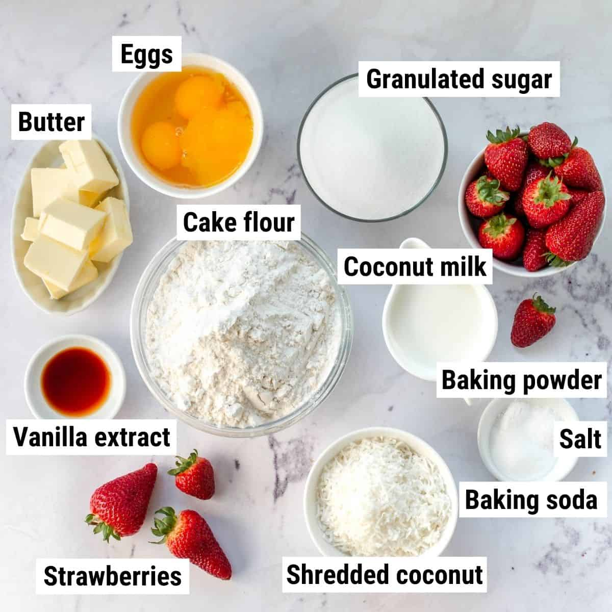 The ingredients to make coconut strawberry cake laid out on a table.