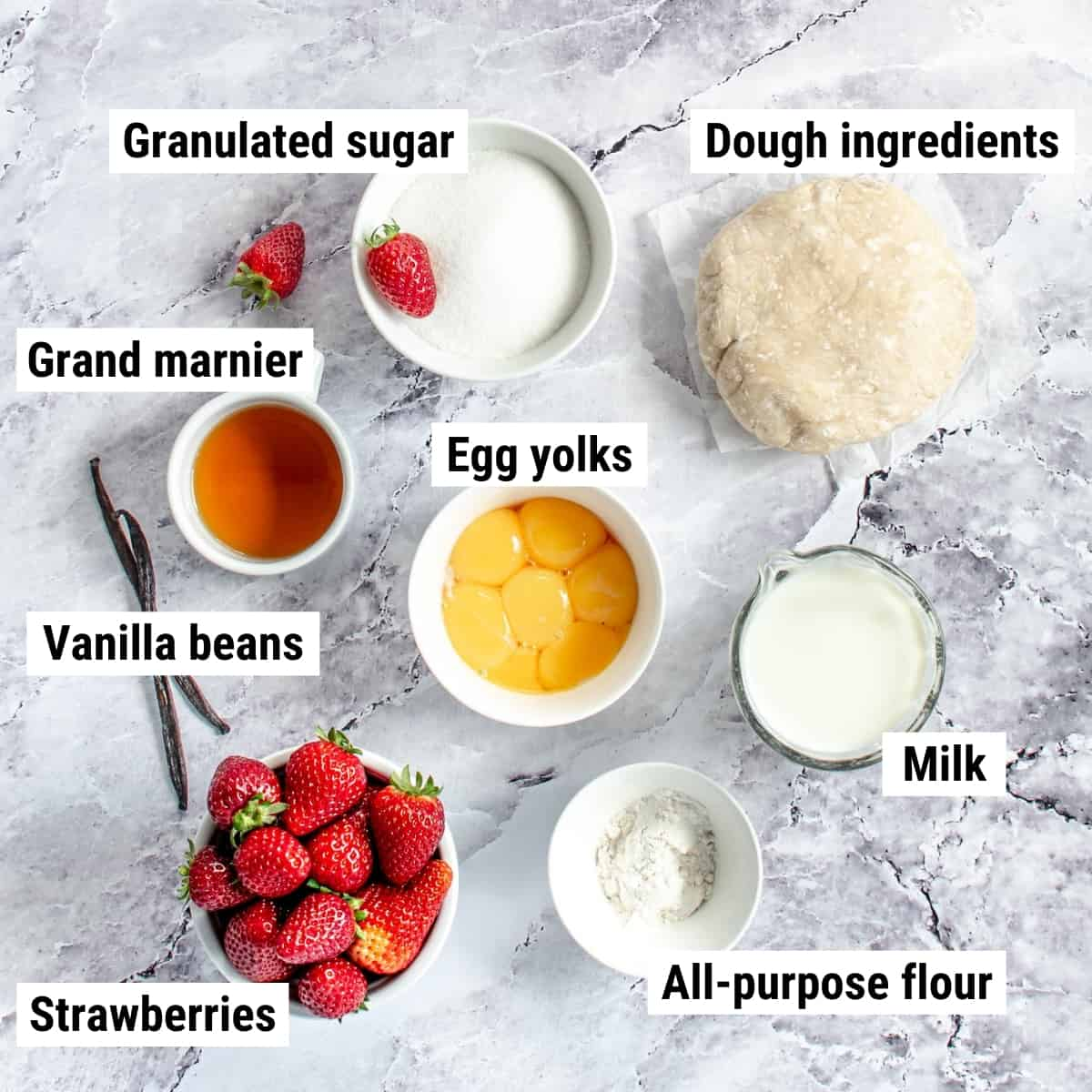 The ingredients used to make strawberry custard tart laid out on a table.