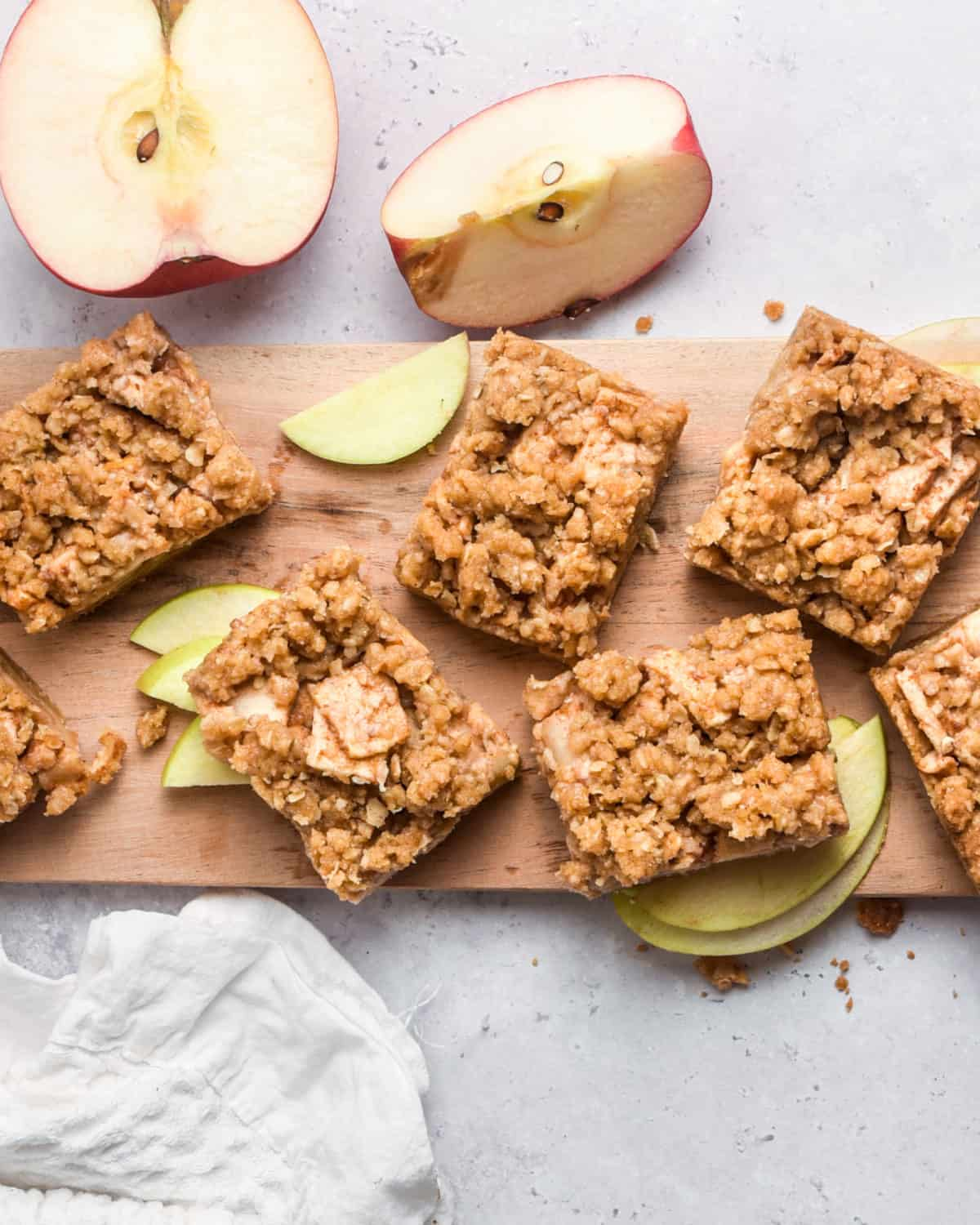 An overhead shot of several apple bars on a cutting board.