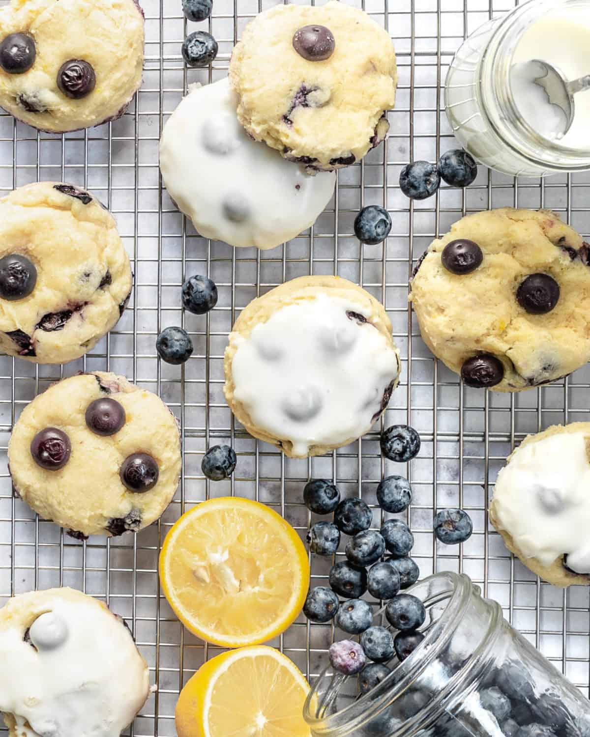 Several blueberry cookies with lemon on a cooling rack.