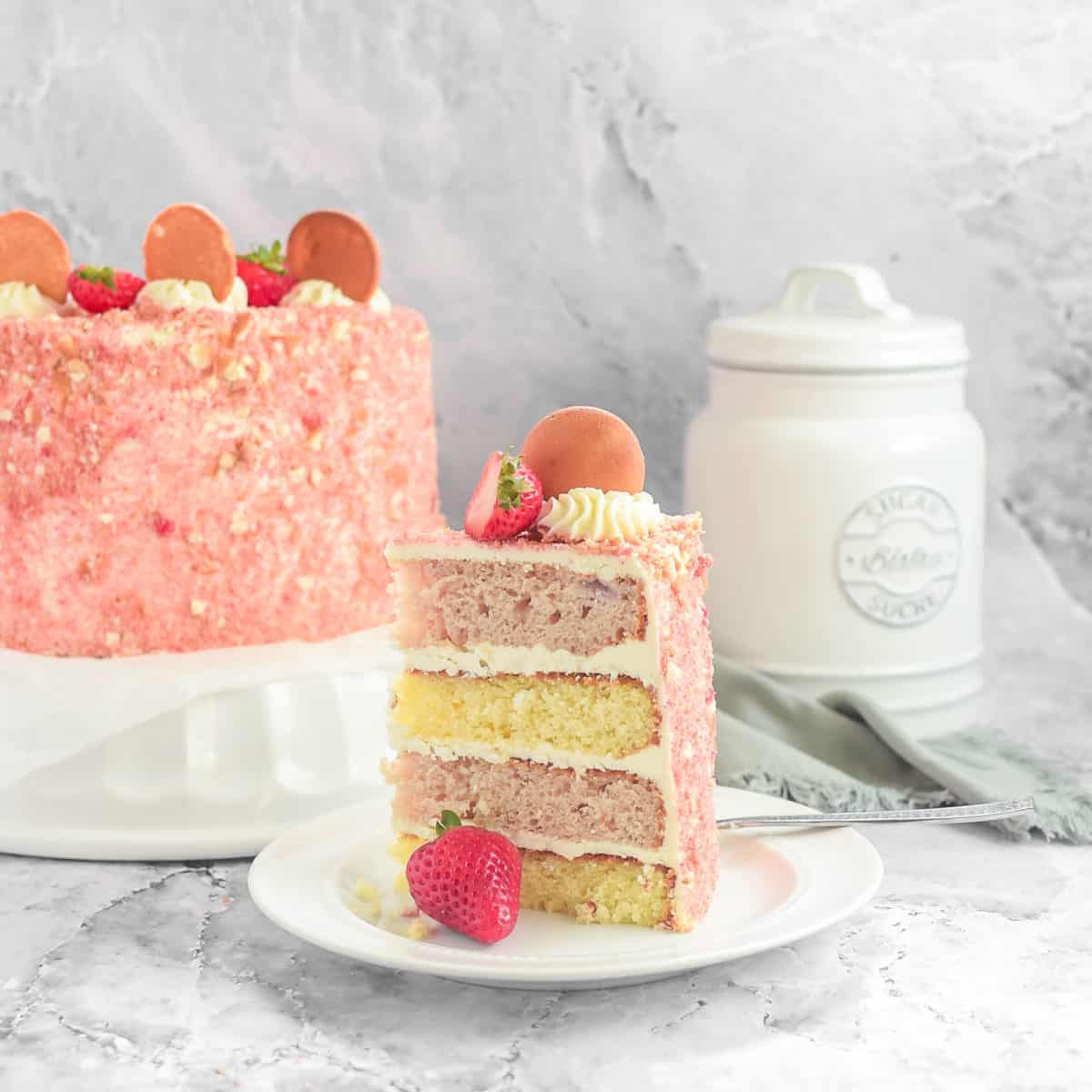 A slice of cake on a plate with fresh strawberries.