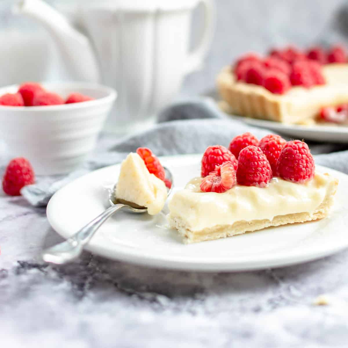 A slice of custard tart on a plate with a spoon and fresh raspberries.