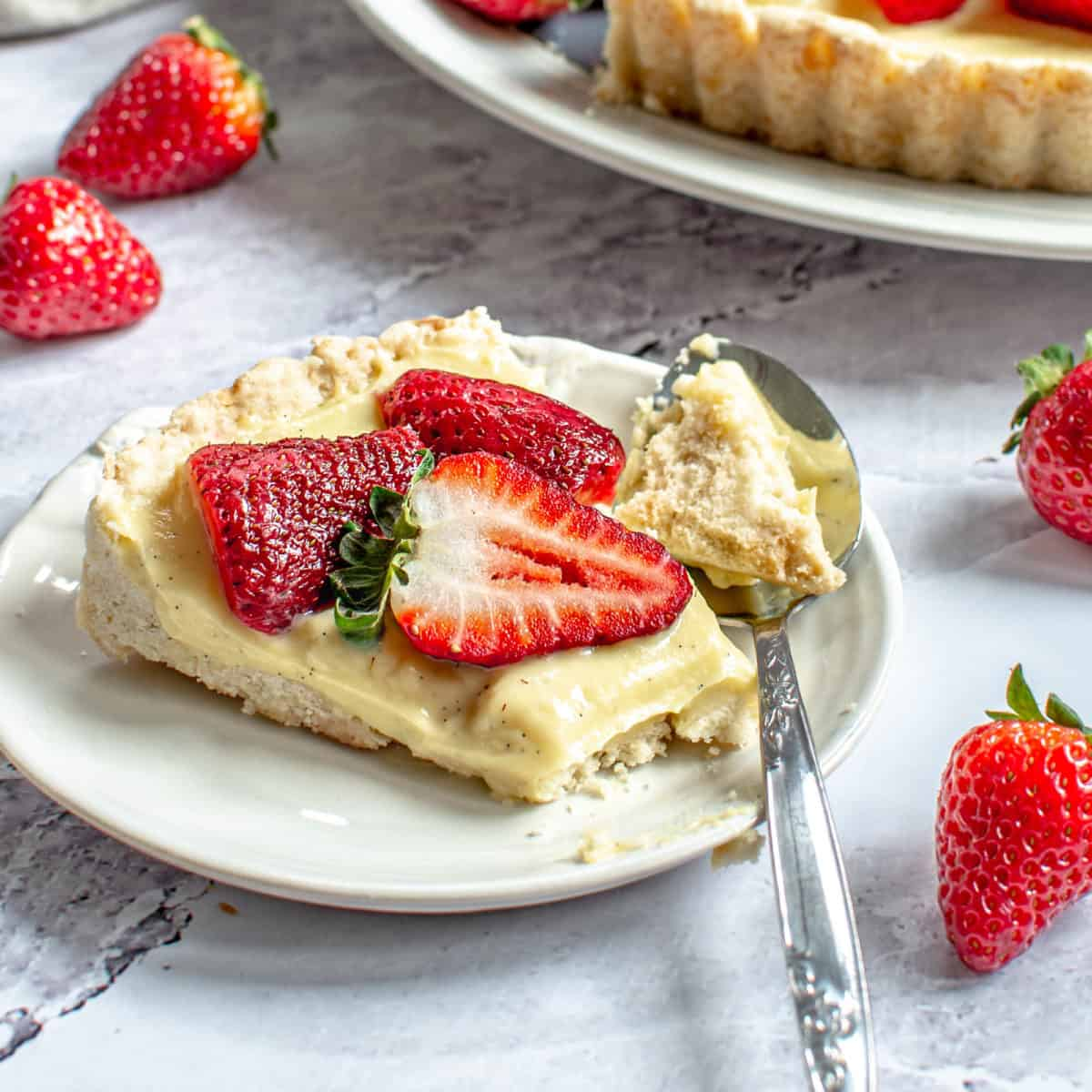 A slice of strawberry custard tart on a plate with a spoon.