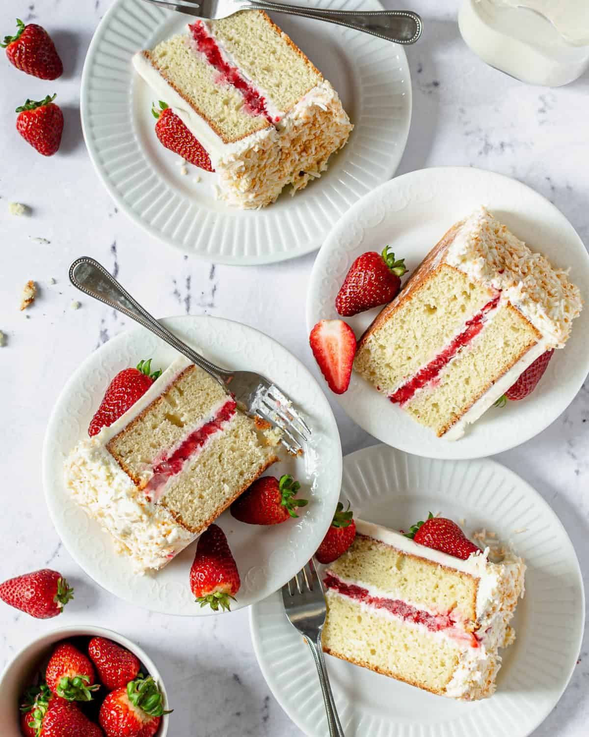Four slices of coconut strawberry cake on plates with forks.