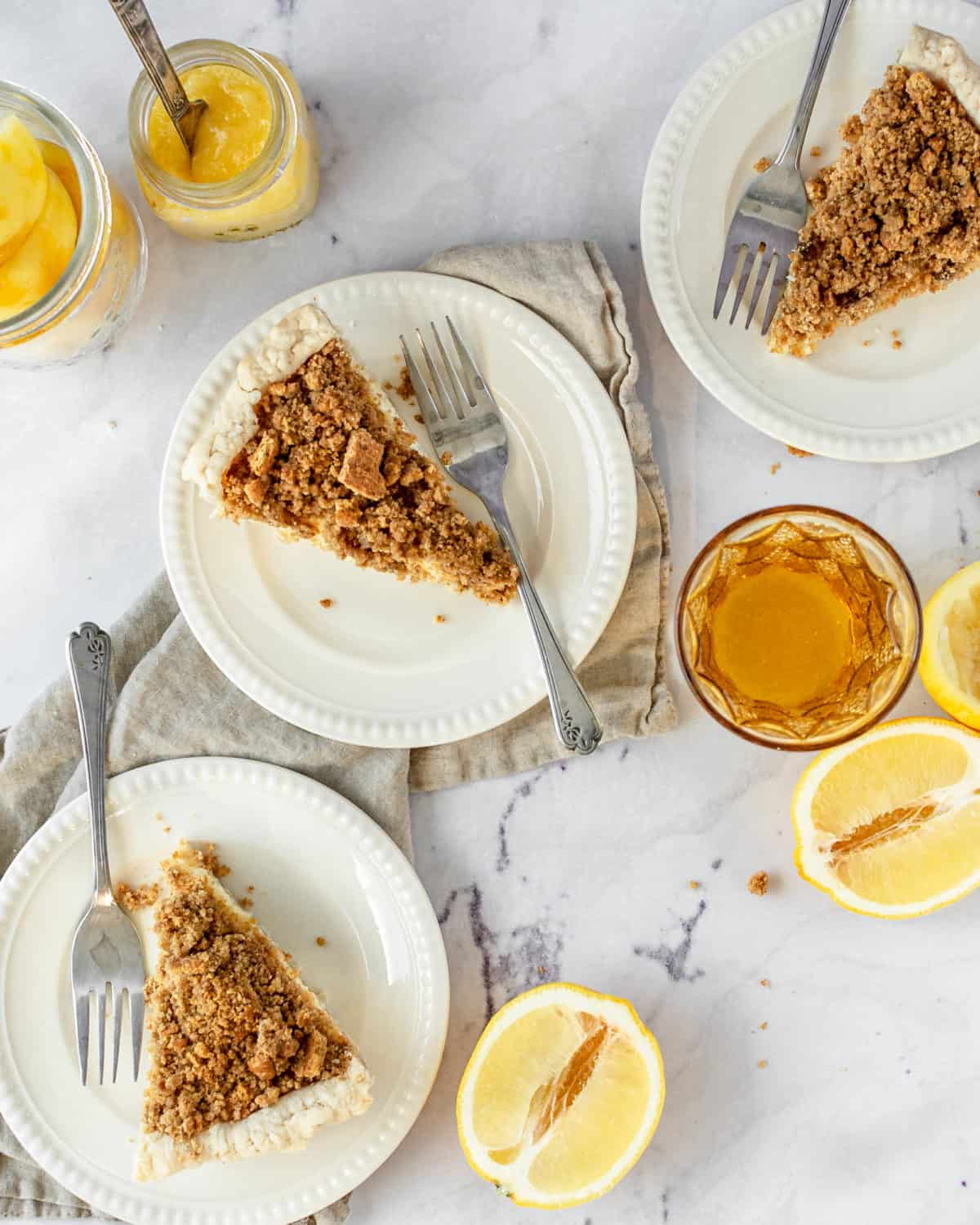Three slices of lemon crunch pie on plates with forks on a table.