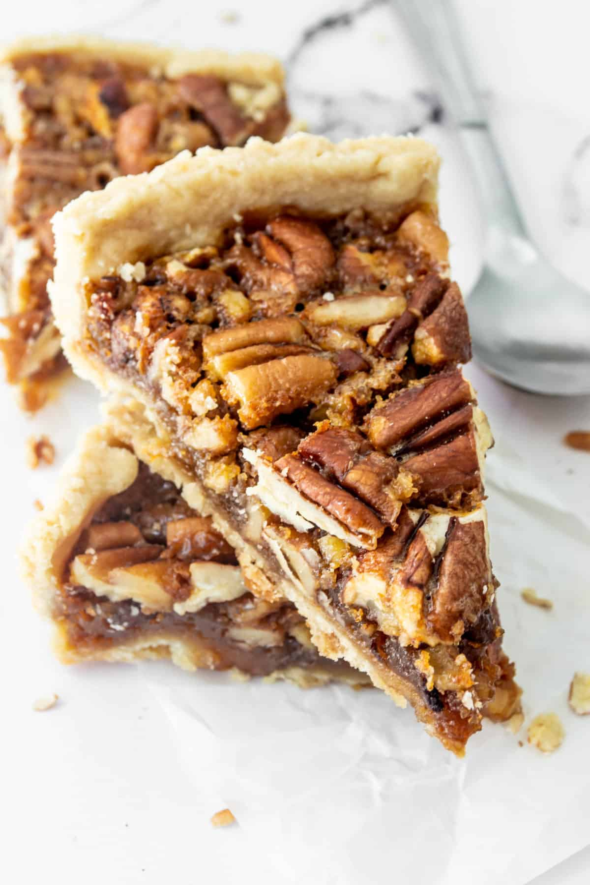 Multiple slices of pecan pie on a table.