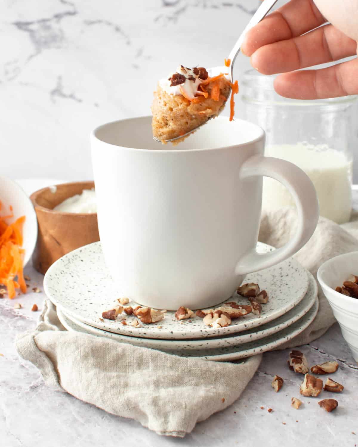 A spoonful of carrot mug cake with almonds.