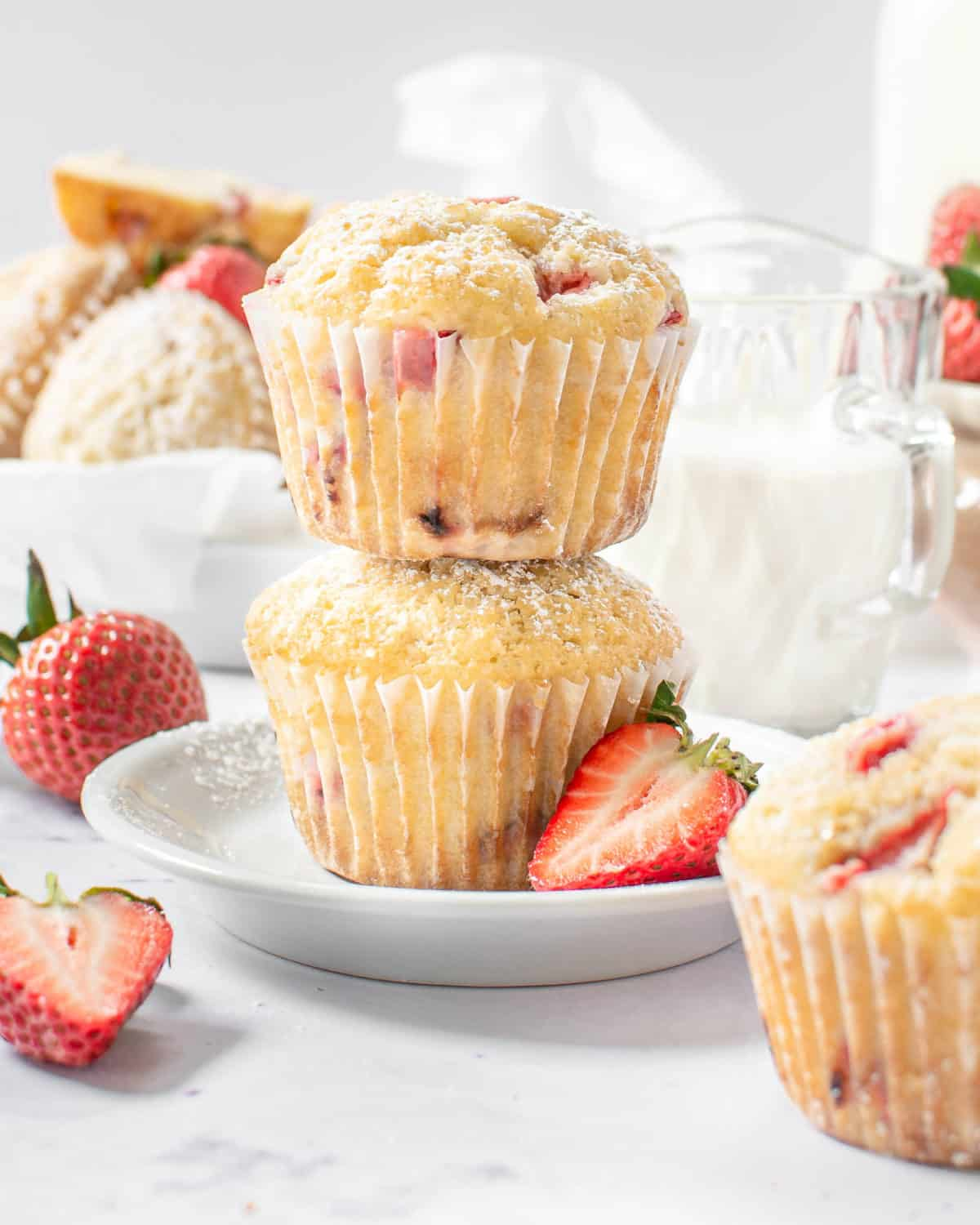 Two strawberry lemon muffins stack on each other.