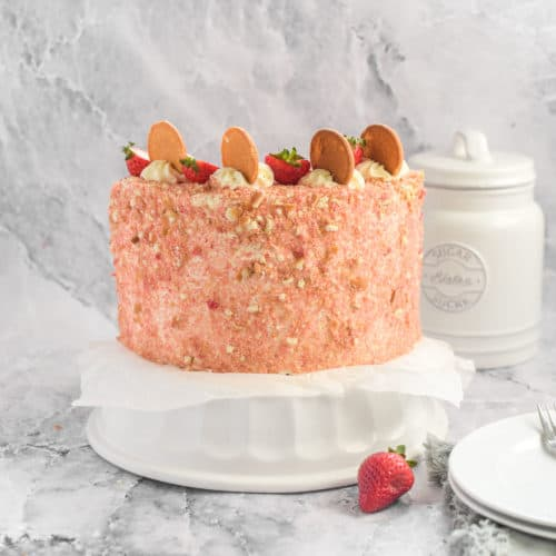 A strawberry crunch cake on a stand.