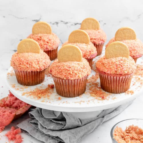 Several strawberry crunch cupcakes on a stand.