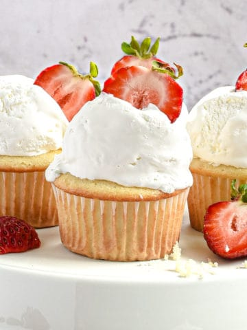 Three strawberry filled cupcakes displayed on a cake stand.