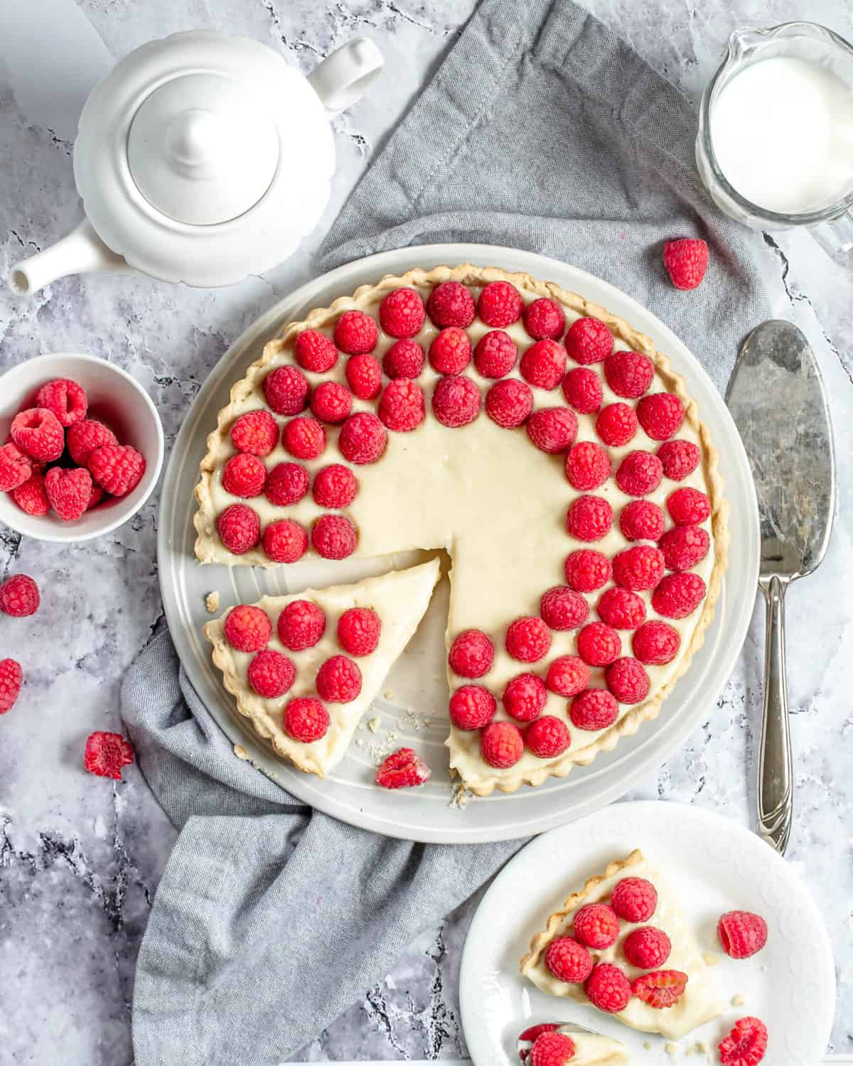 An overhead shot of raspberry custard tart ready to be served and a slice on a plate.