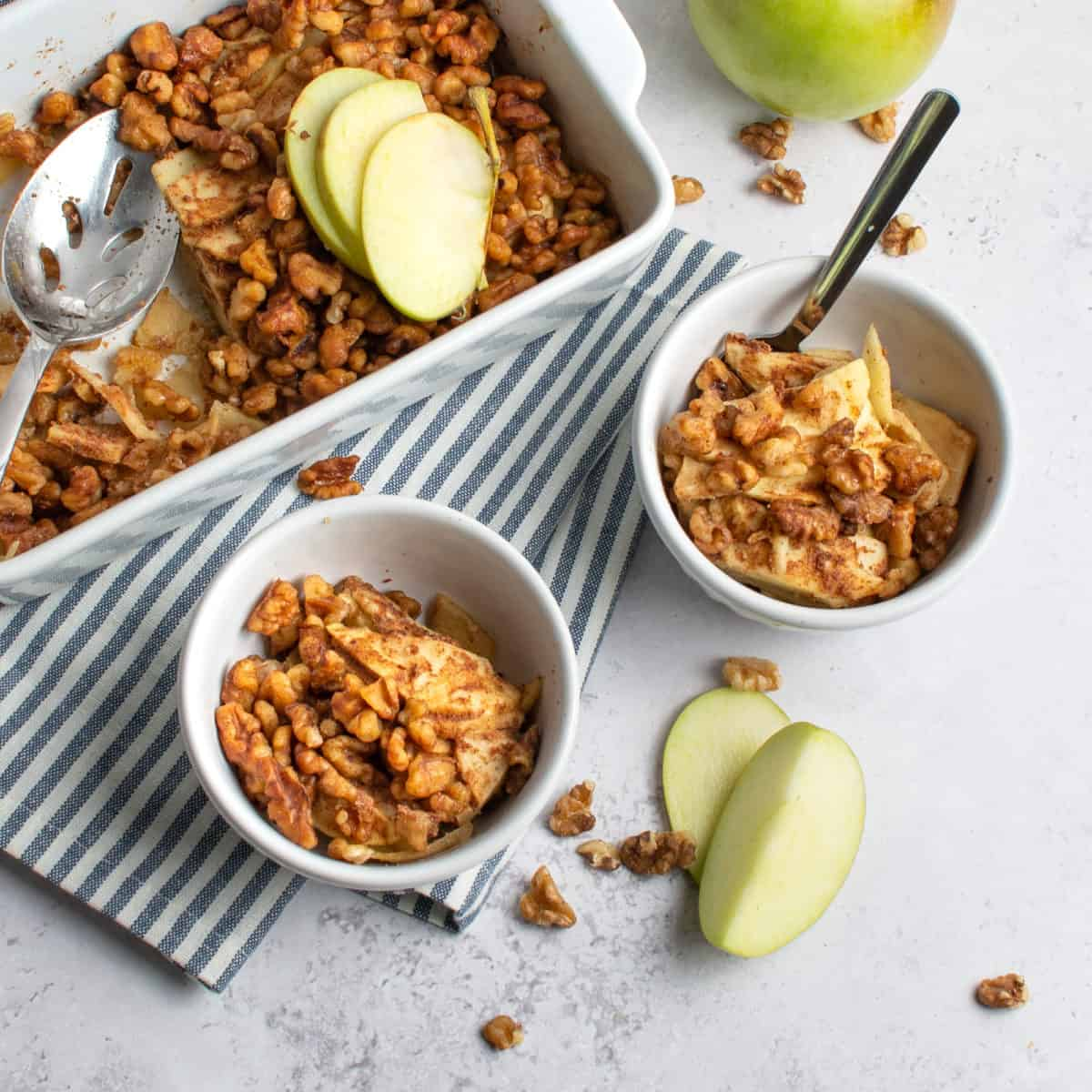 Finished apple crisp in a baking dish being scooped into serving bowls.