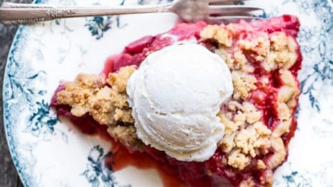 A slice of strawberry crumble pie on a plate.